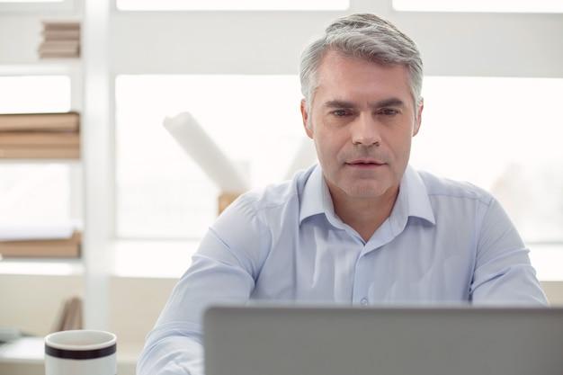 Escritório moderno. homem adulto bonito sério olhando para a tela do laptop e trabalhando enquanto está no escritório