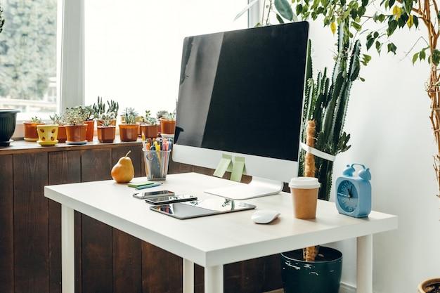 Escritório ou espaço de trabalho em casa, monitor de computador com tela preta na mesa de escritório com suprimentos