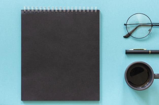 Escritório ou local de trabalho em casa. bloco de notas de cor preta, xícara de café, óculos, caneta azul
