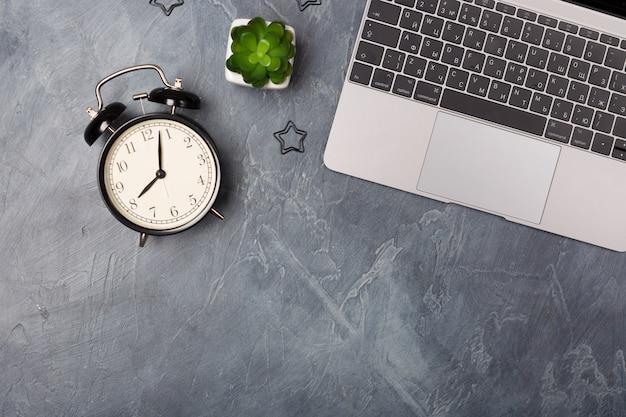 Escritório plano colocar mesa cinza com prata laptop, caneca de café e artigos de papelaria