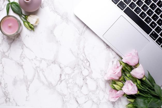 Escritório romântico com flores, vela e teclado em uma mesa de mármore