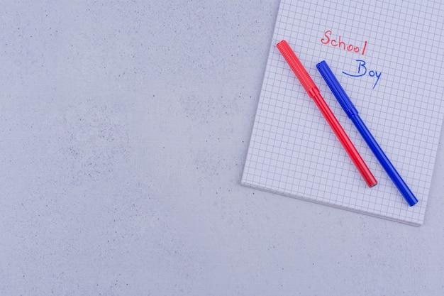 Escritos em papel em branco com canetas vermelhas e azuis.