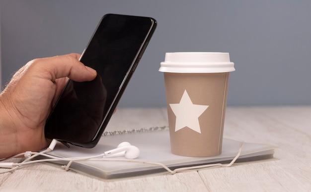 Escriturário manipula copo móvel de café quente com fones de ouvido e pasta