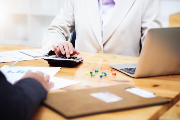 Escriturário usando calculadora com computador portátil, orçamento e papel de empréstimo no escritório. conceito de contabilidade empresarial.