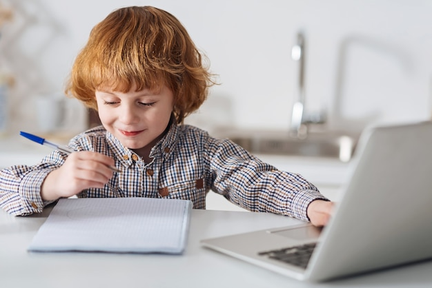Escriturinha talentosa. garoto adorável e diligente e criativo procurando algo on-line e escrevendo enquanto está sentado à mesa em uma cozinha