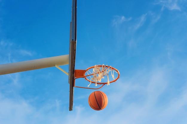 Escudo de basquete, bola voando para cesta no fundo do céu azul