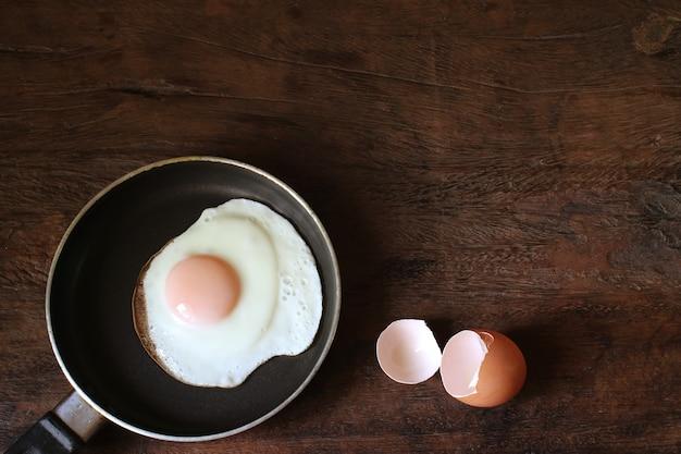 Escudo do ovo frito e de ovo na tabela de madeira.