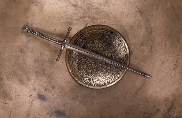 Escudo e espada antigos em um fundo de metal