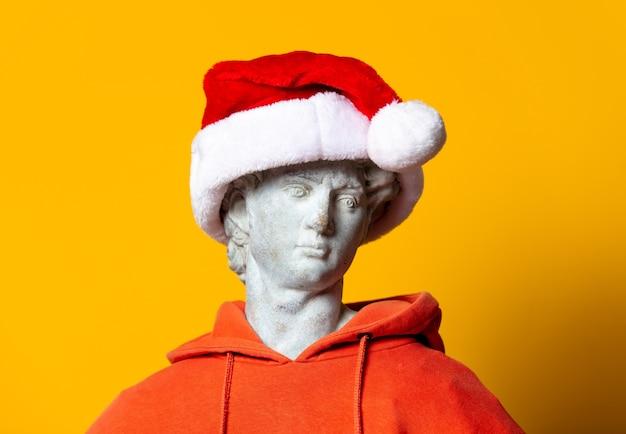 Escultura adolescente com capuz laranja e chapéu de natal em fundo amarelo