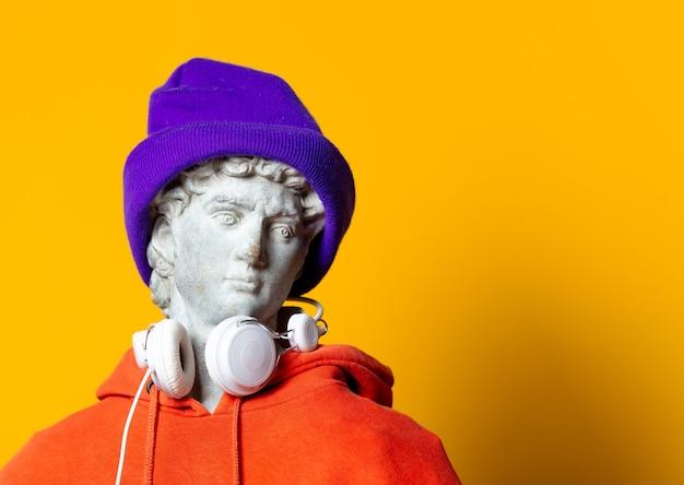 Escultura adolescente com capuz laranja e fones de ouvido no fundo amarelo