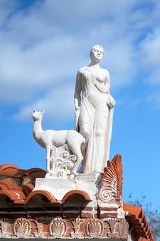 Escultura branca feita de pedra no estilo da grécia antiga, mulher com um animal localizada na beira do telhado de um edifício na grécia