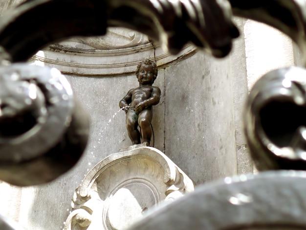Escultura de bronze de manneken pis como vista através da cerca de ferro