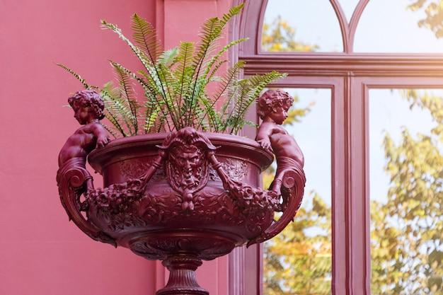 Escultura de cupido no canteiro. vaso de flores romanas, vaso com esculturas no jardim botânico do porto, portugal