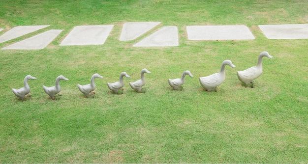 Escultura de decoração de patos cerâmicos na grama verde