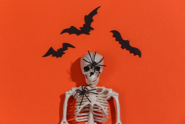 Escultura de esqueleto, aranha e morcegos em fundo laranja brilhante. tema de halloween.