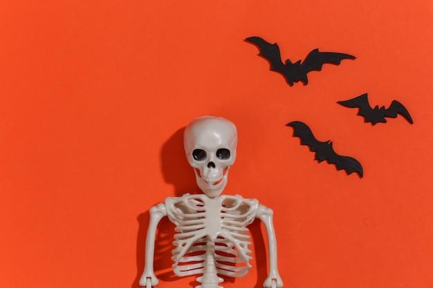 Escultura de esqueleto e morcegos em fundo laranja brilhante. tema de halloween.