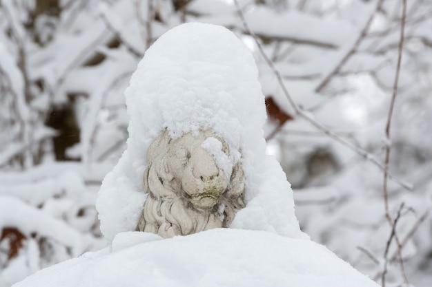 Escultura de leão coberta de neve no parque