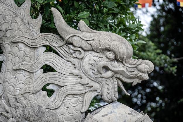 Escultura de pedra do dragão na entrada de um templo budista