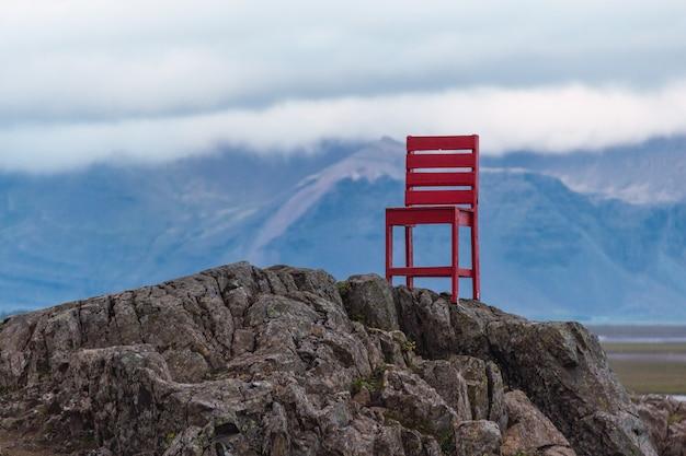 Escultura de uma cadeira vermelha nas rochas perto da cidade