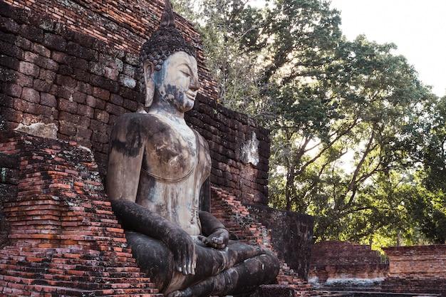 Escultura que está a imagem de buddha de wat mahathat no parque nacional de sukhothai em tailândia no por do sol.