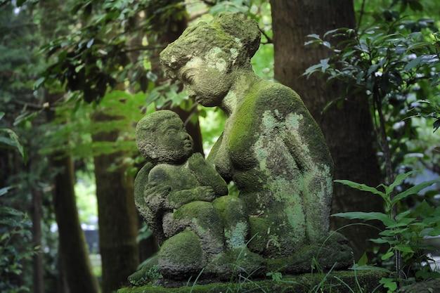 Esculturas de pedra de mãe e filho dentro da escura floresta japonesa