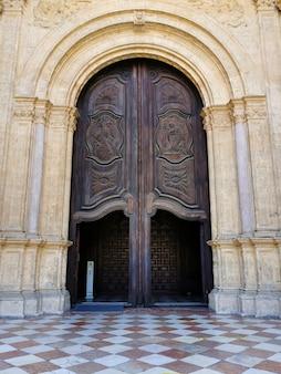 Esculturas em madeira decoram uma das portas da catedral de málaga, na andaluzia, espanha.