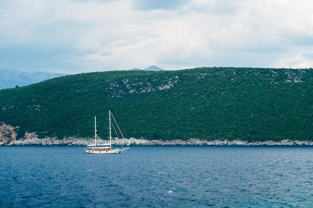 Escuna branca de dois mastros navega ao longo da costa rochosa com montanhas ao fundo