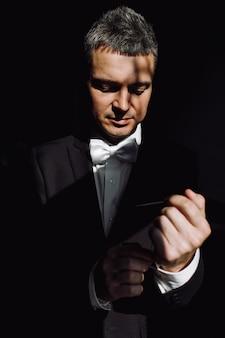 Escuridão esconde noivo bonito enquanto ele conserta sua jaqueta