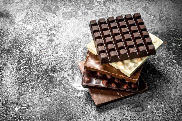 Escuro, branco e chocolate com nozes na mesa rústica.
