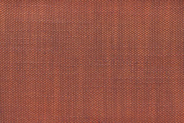 Escuro - fundo alaranjado de matéria têxtil, close up. estrutura da macro de malha.