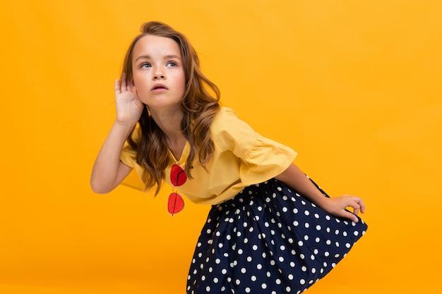 Escutas de menina em uma conversa, uma criança segura uma palma pela orelha contra a parede laranja