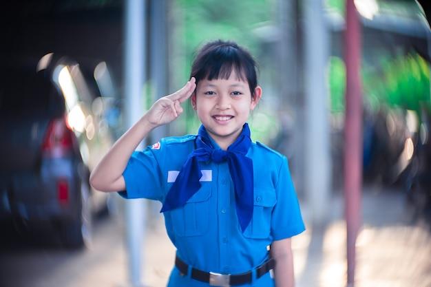 Escuteira asiática de uniforme levanta três dedos para respeitar com um belo bokeh