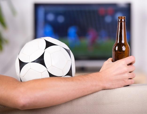 Esfera de futebol do close-up e mão com uma cerveja.