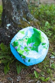 Esfera do globo arruinada na grama