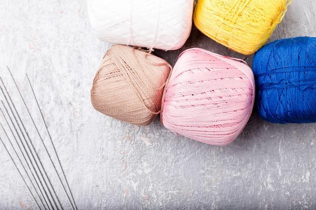 Esfera e agulhas de confecção de malhas multicolor no fundo cinzento. vista do topo. copie o espaço. fios de tricô.