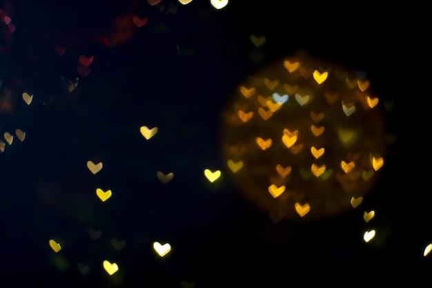 Esfera laranja bokeh abstrato e forma de coração desfocada amor dia dos namorados luz noturna colorida na parede de shopping center