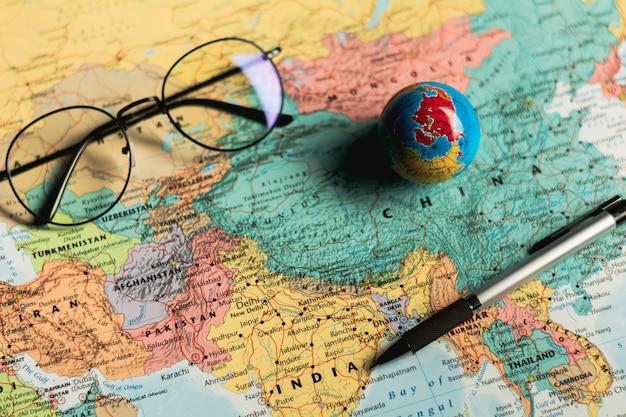 Esfera pequena do globo do mundo, vidros e uma pena no mapa.