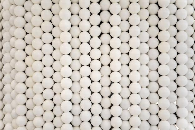 Esferas brancas pequenas e parede lisa das formas do círculo para o design de interiores.