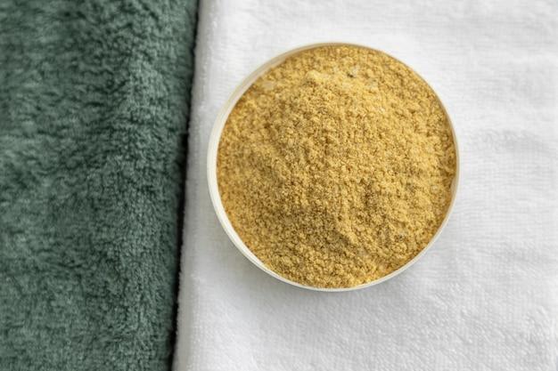 Esfoliação corporal natural em toalhas brancas e de eucalipto.