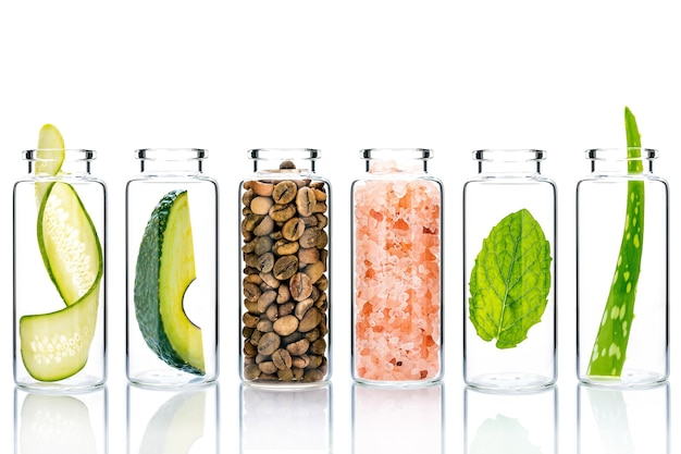 Esfoliantes caseiros com ingredientes naturais em frascos de vidro isolam em fundo branco.