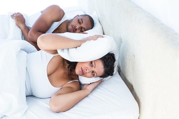 Esforçada esposa dormindo além do marido ronco
