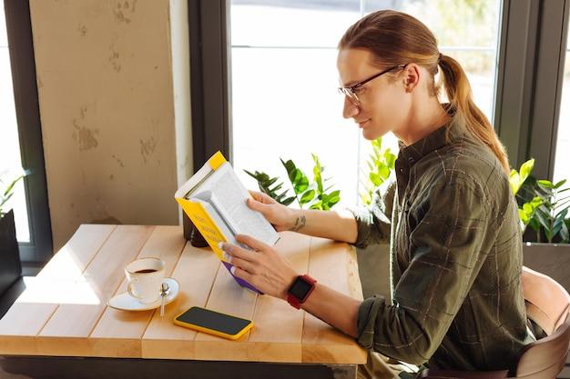 Esforçando-se para o conhecimento. homem bonito e positivo segurando um livro enquanto se concentra na leitura