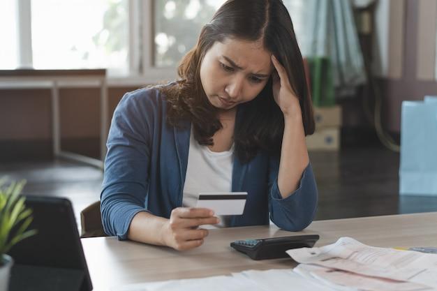 Esforço asiático da mulher com débito do cartão de crédito.