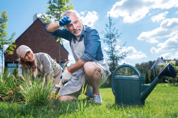 Esfregando as sobrancelhas. homem barbudo de cabelos grisalhos enxugando as sobrancelhas depois de trabalhar duro perto de uma cama de jardim com sua atraente esposa