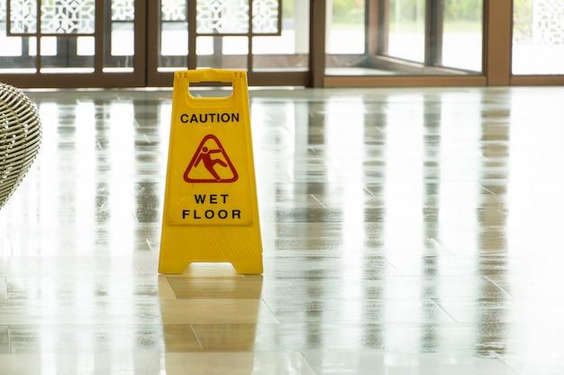 Esfregando o chão molhado no lobby do hotel. plano de fundo para piso molhado de cuidado.