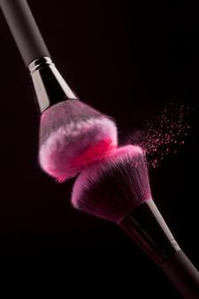 Esfregando pincéis de maquiagem profissional com pó rosa