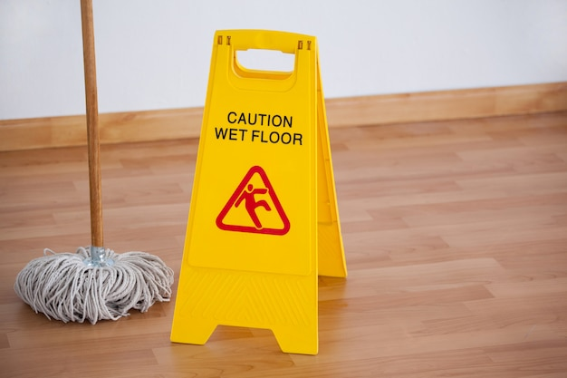 Esfregão com sinal de cuidado de piso molhado