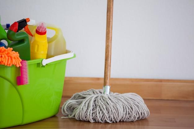 Esfregão e equipamento de limpeza no piso de madeira