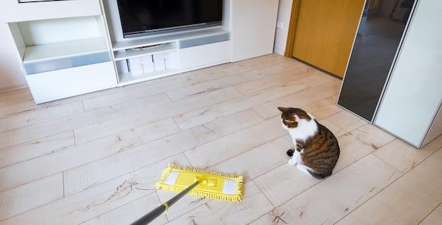 Esfregona de microfibra amarela isolada na superfície do piso de madeira branca, closeup, dentro de casa