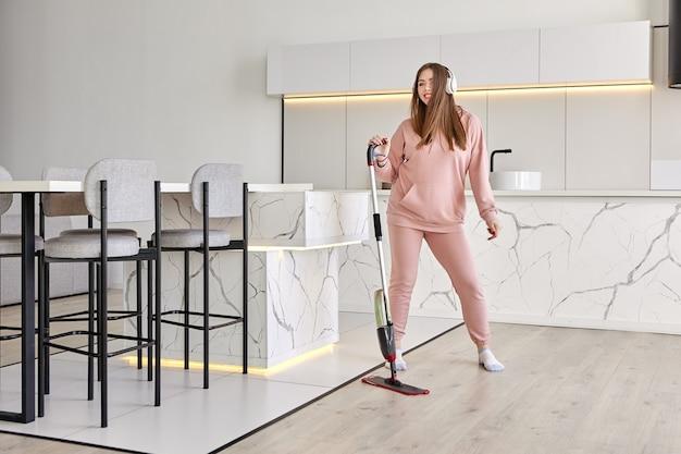 Esfregona plana com spray e almofada de microfibra nas mãos de uma jovem que está ouvindo música, arrumando e dançando na cozinha.